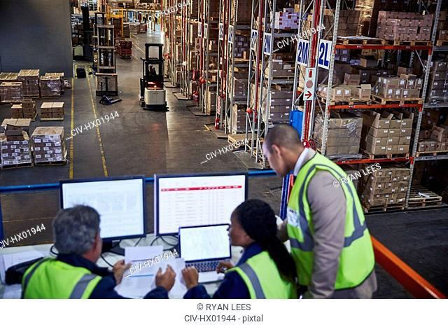 Managers working meeting at laptop and computers in distribution warehouse