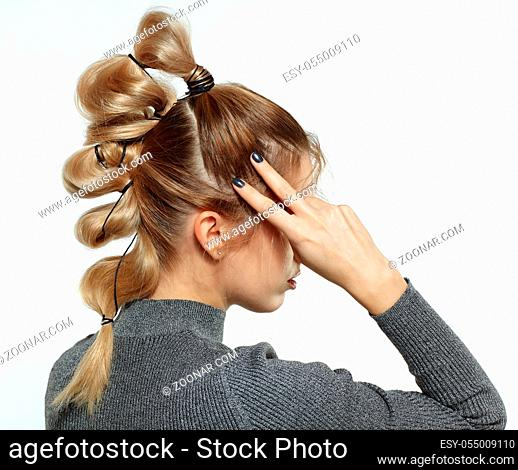 Back view portrait of beautiful young dark blonde woman. Female with creative braid hairdo on gray background