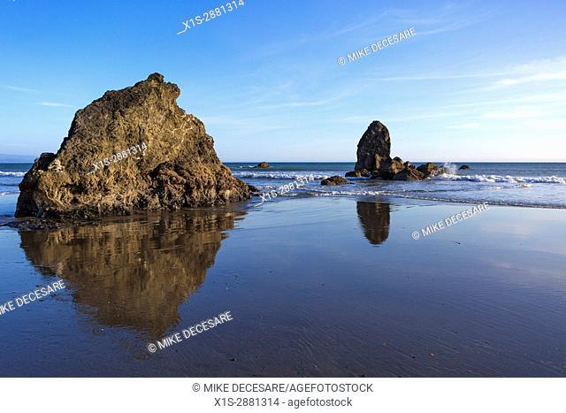 Sunset creates a mirror image reflection of sea stacks along the coast of Oregon