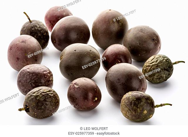 Fourteen whole passion fruits of the dark purple variety placed on a white table top. Tropical and subtropical berry fruit of Passiflora edulis