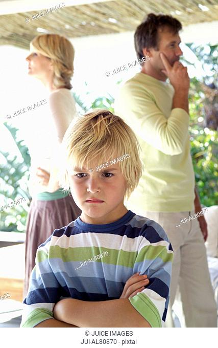 Parents arguing with son looking sad