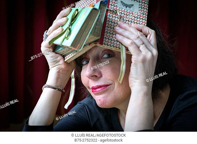 Middle-aged woman with a book over her head smiling and looking at the camera