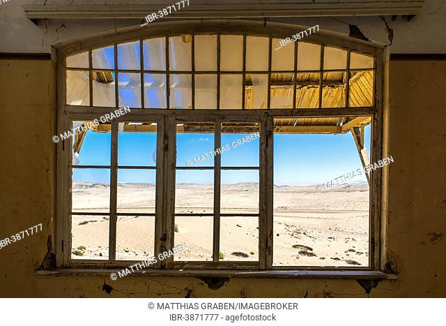 View through a window of an abandoned house in a former diamond miners settlement that is slowly covered by the sand of the Namib Desert, Kolmanskop, ?Karas