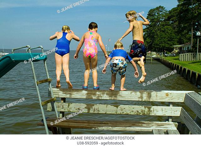 Two girls and two boys jumping into the Albemarle Sound from the dock