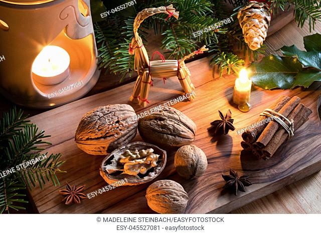 Christmas decoration - walnuts, candles, cinnamon sticks, star anise, fir branches, and straw ornaments