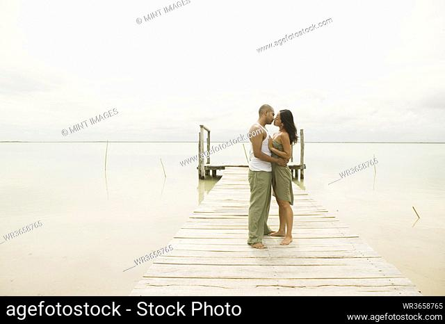 Couple kissing on a pier