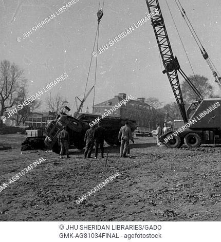 During the early stages of construction of the Milton S Eisenhower Library at Johns Hopkins University, a half dozen workers in uniform use a large crane to...