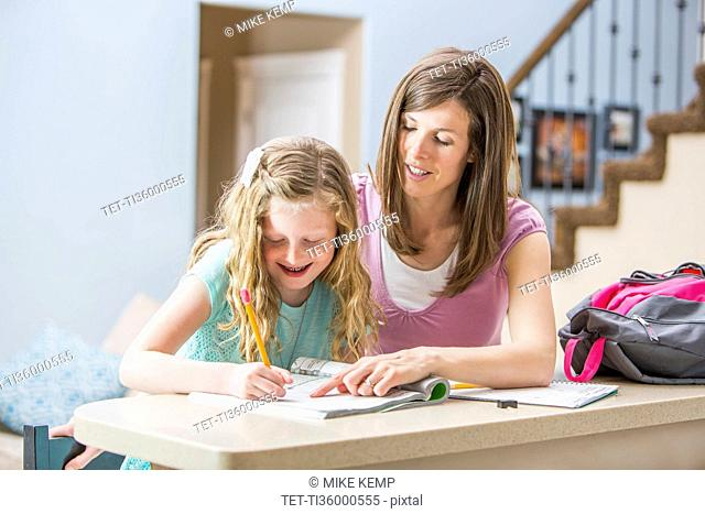 Mother and daughter (8-9) sitting at table doing homework