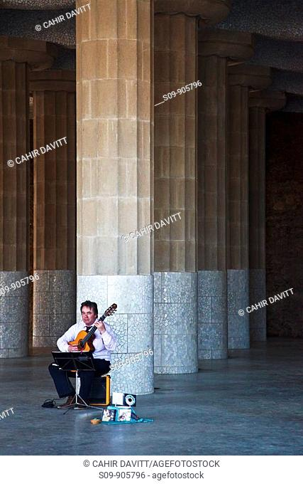Spain, Cataluna, Barcelona, El Coll, A male lone guitar player plays his guitar in Parc Guell designed by the architect Antoni Gaudi