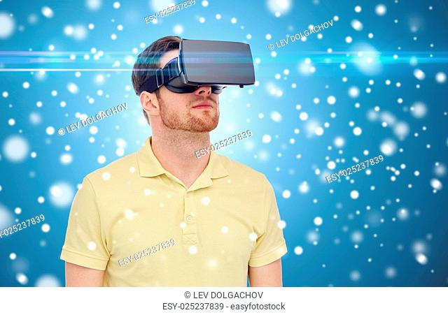 technology, augmented reality, winter, christmas and people concept concept - young man with virtual headset or 3d glasses over snow on blue background and...