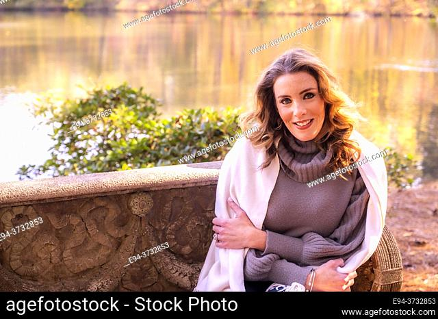 A pretty 38 year old woman outdoors, sitting on a stone bench, wrapped in a blanket, in a park setting