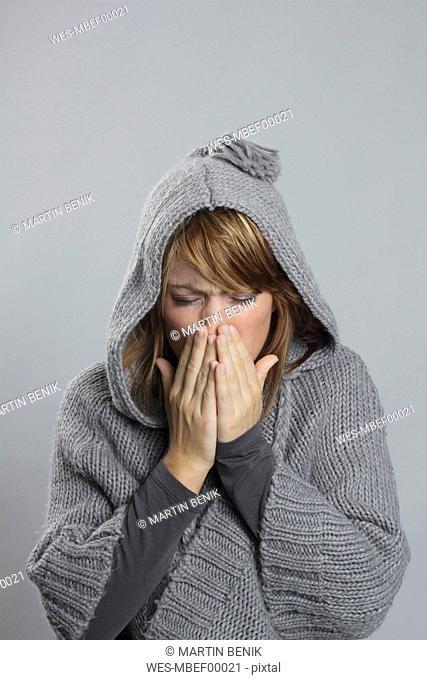 Woman sneezing looking down, portrait