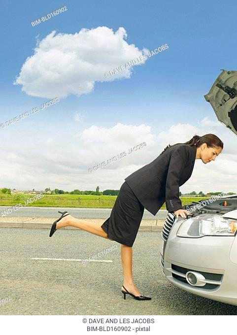 Caucasian businesswoman examining broken-down car engine on rural road