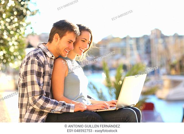 Couple using a laptop in a sunny coast town