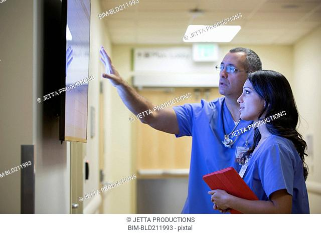 Doctors watching monitor in hospital corridor