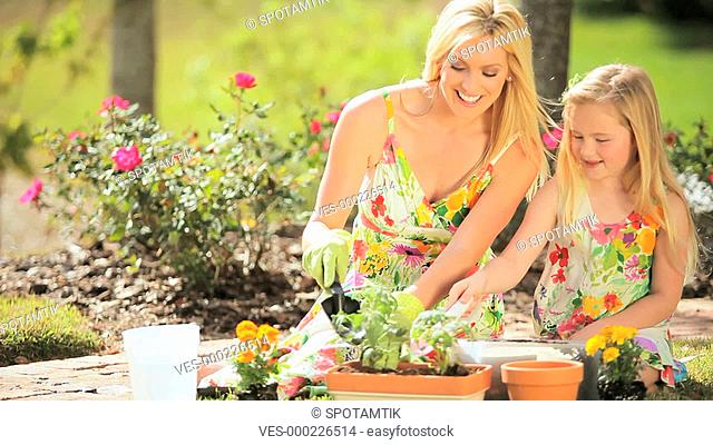 Pretty blonde mother & little daughter happily potting plants in the garden