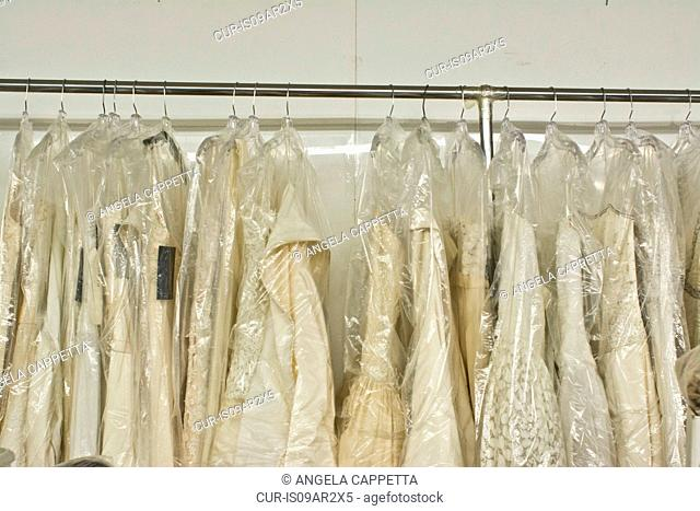 Clothes rail of wedding gowns protected with plastic bags in fashion design studio