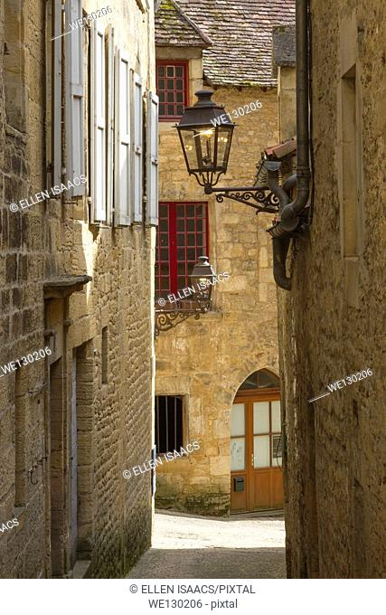 Wrought iron street lamps and windows on medieval sandstone buildings in charming Sarlat, Dordogne region of France