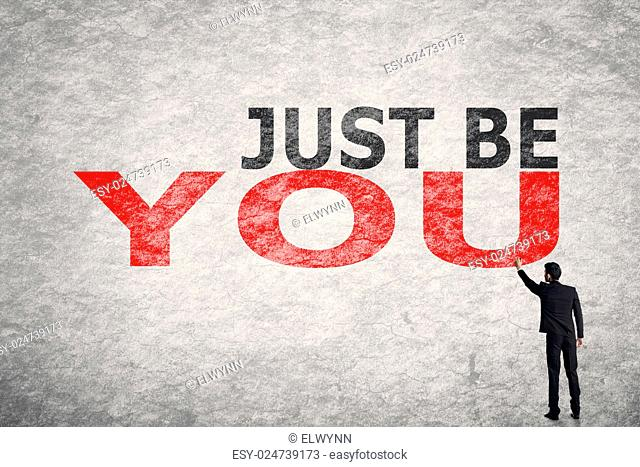 Asian businessman write text on wall, Just Be You