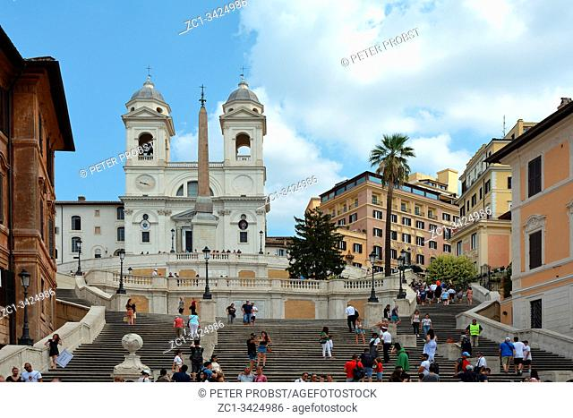 Tourists on the Spanish steps at the Piazza di Spagna in Rome with the church Trinita dei Monti - Italy