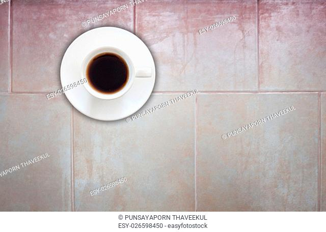 Top view of coffee cup on ceramic tiles wall texture background