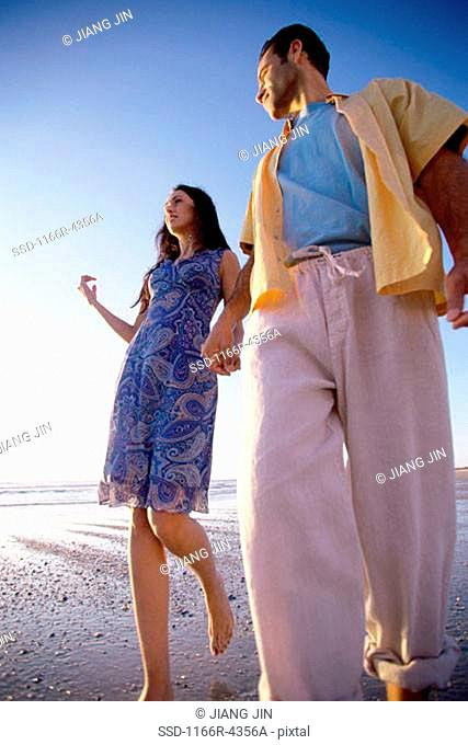 Low angle view of a young couple walking together at the beach