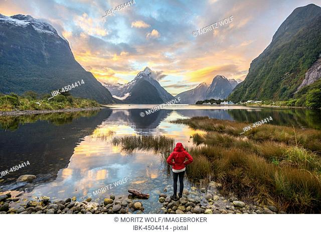 Tourist looking at the landscape, Miter Peak reflected in the water, sunset, Milford Sound, Fiordland National Park, Te Anau, Southland Region, Southland