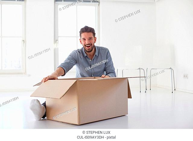 Portrait of young man sitting on floor opening cardboard box in new house