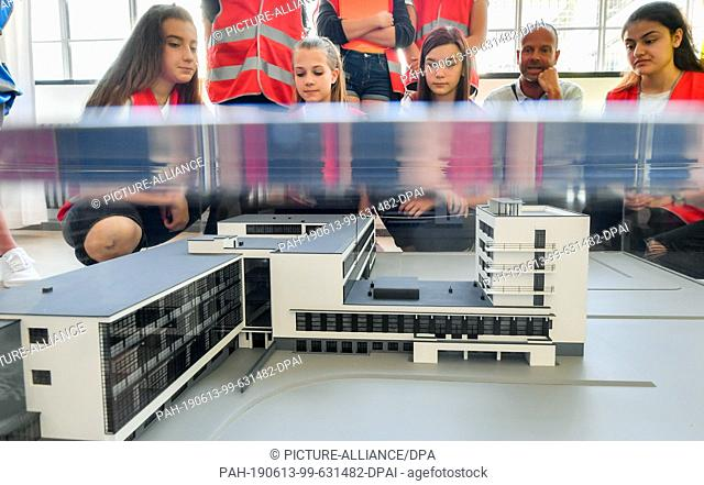 13 June 2019, Saxony-Anhalt, Dessau-Roßlau: Together with Bauhaus guide Carsten Brinzing, students from the Dessau Peace School look at a model of the Bauhaus...