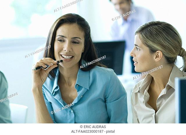 Two businesswomen working together in office, one holding pen up to mouth