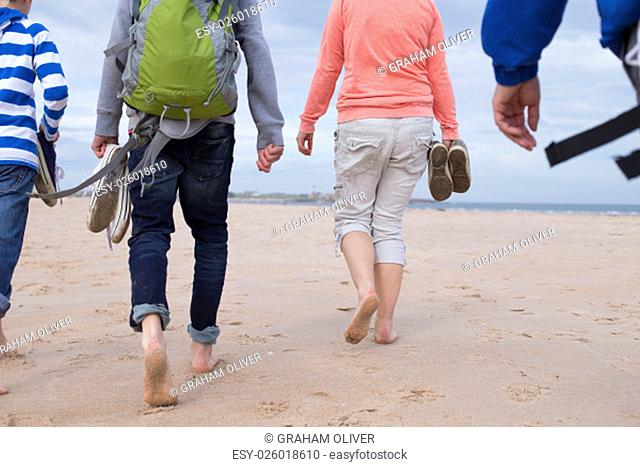 Family of four walking along a beach barefoot. They are wearing warm casual clothing and only their bodies can be seen