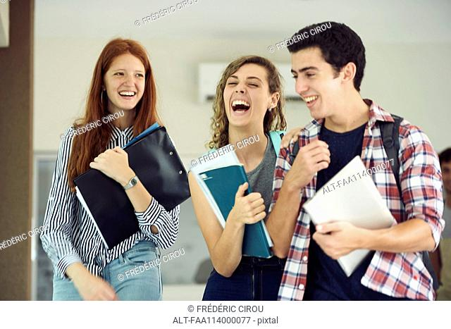 Classmates laughing together while walking in school corridor