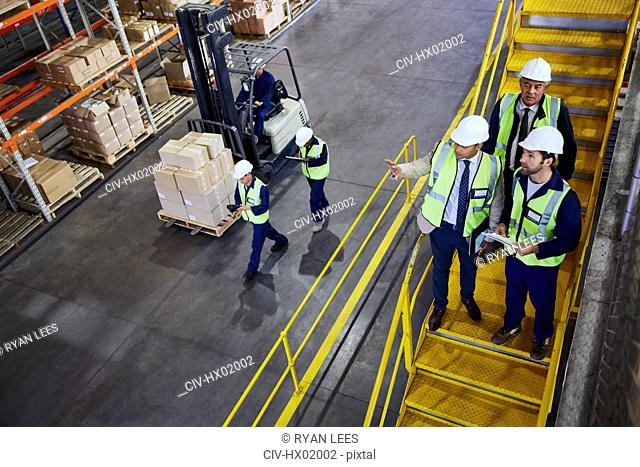 Forklift, managers and workers talking in distribution warehouse