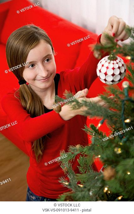 Girl (10-11) decorating Christmas tree