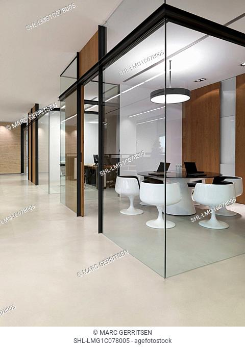 View of small meeting room through glass walls in modern office