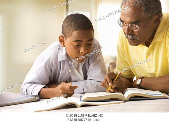 African grandfather helping grandson with homework