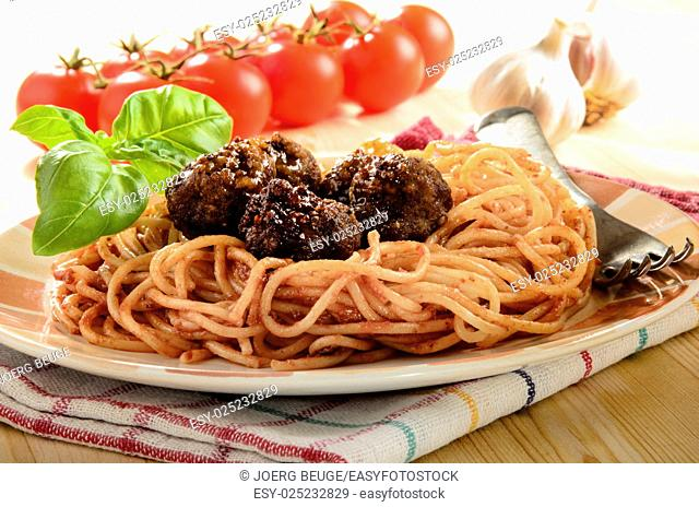 spaghetti with tomato sauce, basil and meat balls on a plate