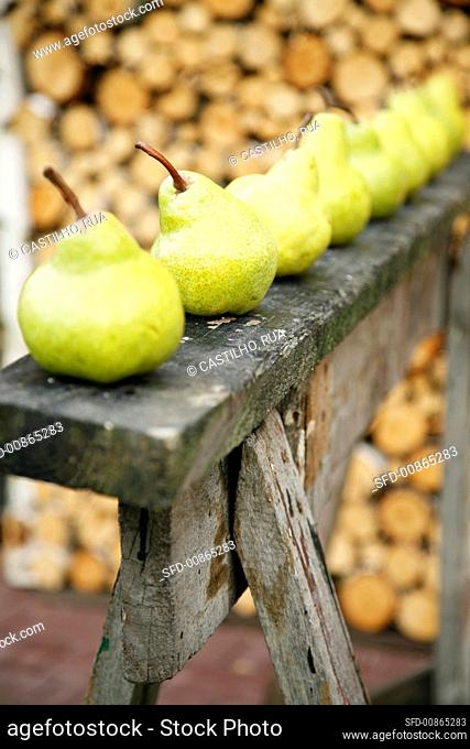 Fresh pears in a row on a wooden structure