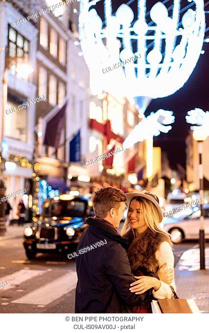 Romantic young couple on New Bond street at xmas, London, UK