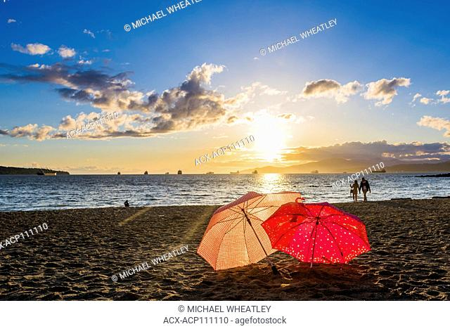 Couple walking on the beach at sunset, English Bay, Vancouver, British Columbia, Canada