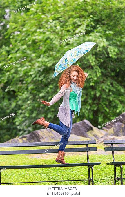 Woman with umbrella dancing on bench in park