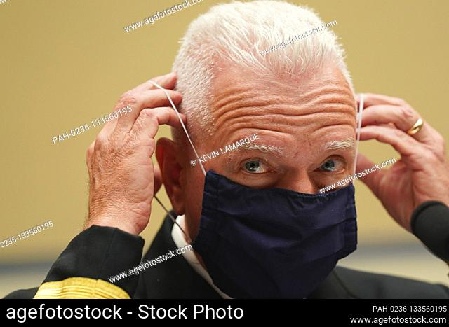 Admiral Brett Giroir, United States Assistant Secretary for Health adjusts his protective face mask as he testifies before a House Select Subcommittee on the...