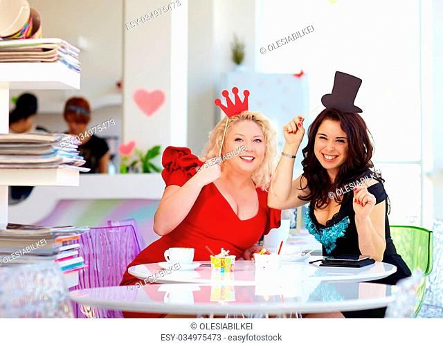 plus size women friends enjoying life, having fun in cafe