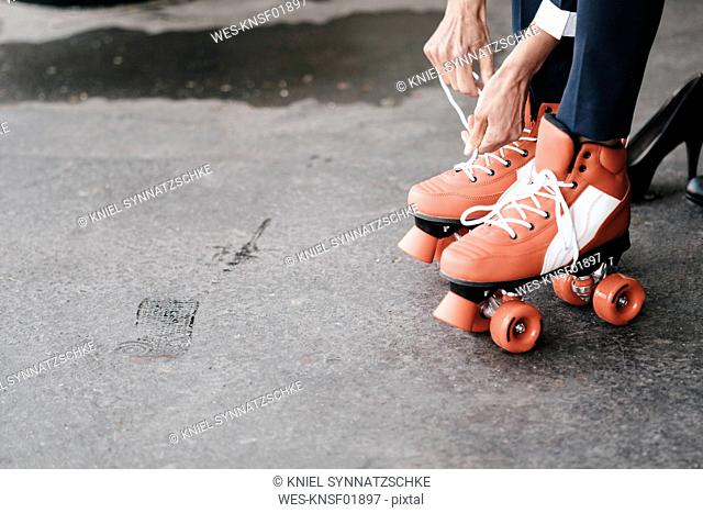 Businesswoman tying her roller skates, close up