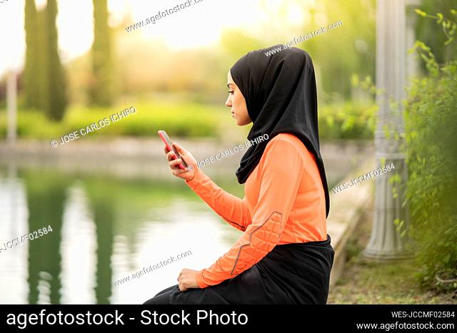 Young woman using smart phone while sitting near pond