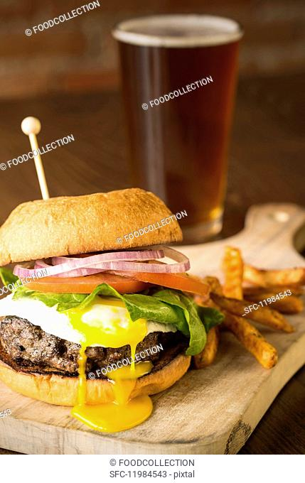 A burger with a fried egg, chips and beer