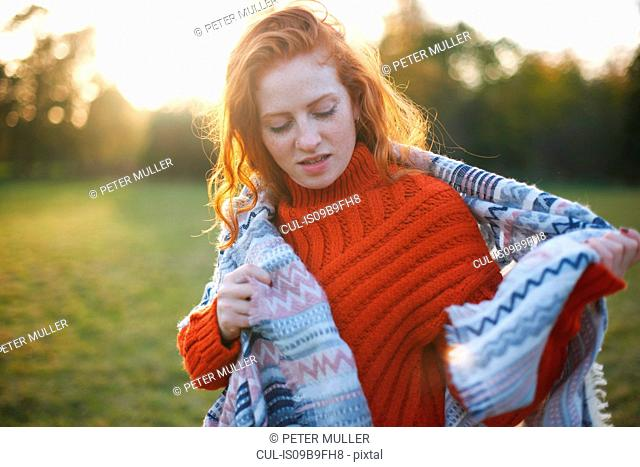 Young woman in rural setting, wrapped in blanket