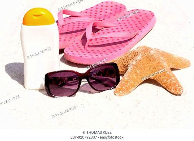 Sonnenmilch und Flip-Flops am Strand