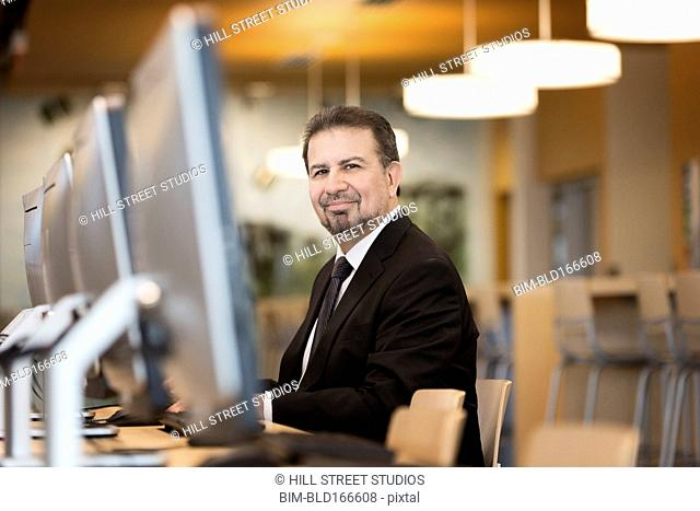 Hispanic businessman using computer in library