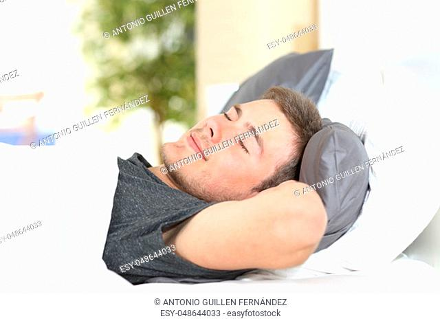 Man sleeping on a comfortable bed at home or hotel